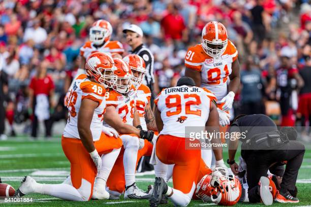 Lions defensive lineman Maxx Forde and teammates kneel around injured teammate BC Lions defensive lineman Mic'hael Brooks [Not Pictured] Canadian...
