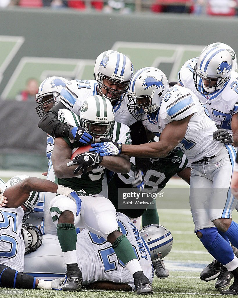 Lions defensive tackle Tyoka Jackson and linebacker Boss Bailey stop Jets rookie runningback Leon Washington during the New York Jets 31 to 24...