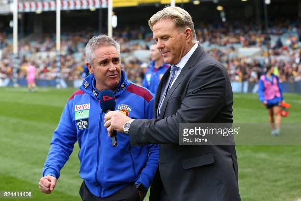Lions head coach Chris Fagan talks wth Dermott Brereton while walking to the coaches box during the round 19 AFL match between the West Coast Eagles...