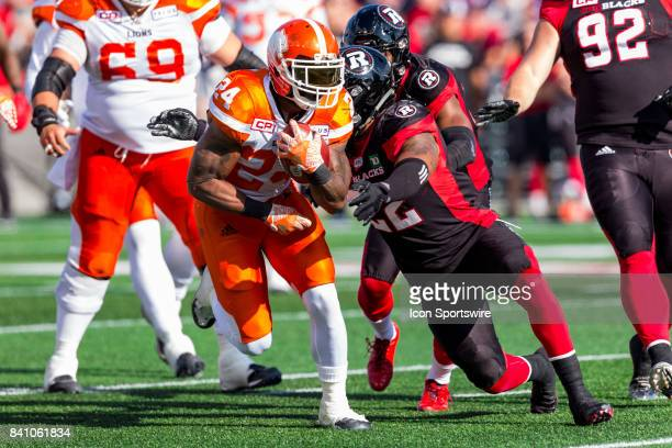 Lions running back Jeremiah Johnson protects the ball as he's about to be hit by Ottawa RedBlacks linebacker Khalil Bass during Canadian Football...