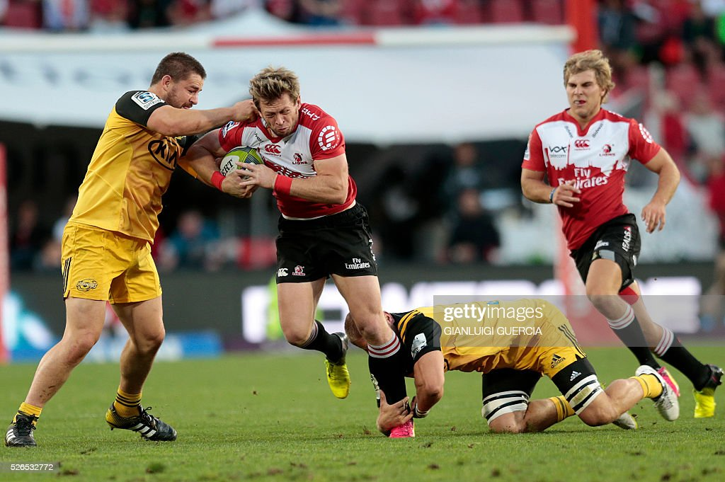 Lions South African fullback Ruan Combrinck (2nd L) is tackled by Hurricanes' New Zealand loose forward Brad Shields (R) and New Zealand hooker Dane Coles (2nd L) during the Super Rugby clash between Lions and Hurricanes at Ellis Park rugby stadium on April 30, 2016 in Johannesburg, South Africa. / AFP / GIANLUIGI