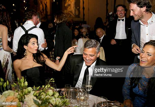 Lior Suchard performs magic for Amal Alamuddin George Clooney and Veronica Berti during the Celebrity Fight Night gala celebrating Celebrity Fight...