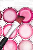 Lip brush resting on pink lip gloss palette, close-up, elevated view