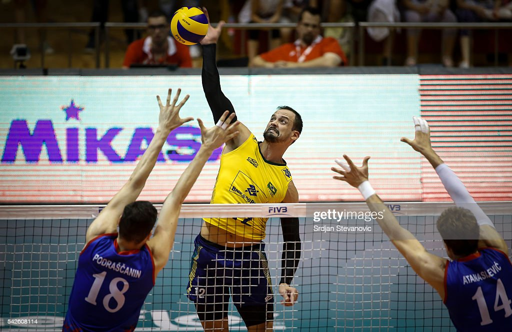 Lipe of Brazil spikes the ball as Marko Podrascanin and Aleksandar Atanasijevic of Serbia attempts to block during the match between Brasil and...