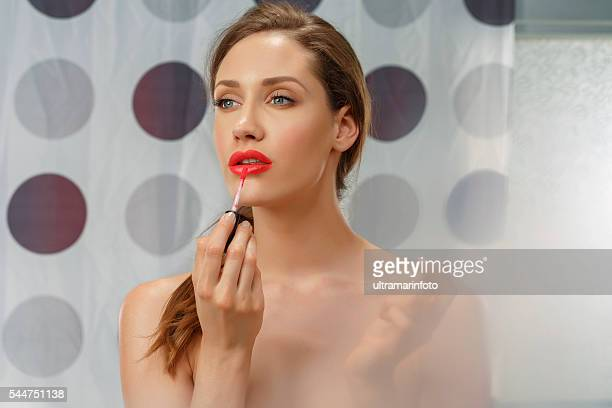 Lips gloss   Beautiful  young women applying lipstick   Bathroom  Beauty