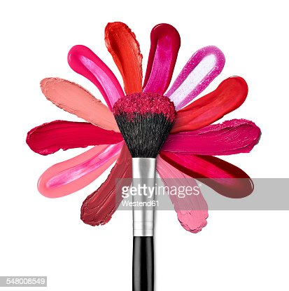 Lipstick and nail polish strokes forming with powder brush a flower shape