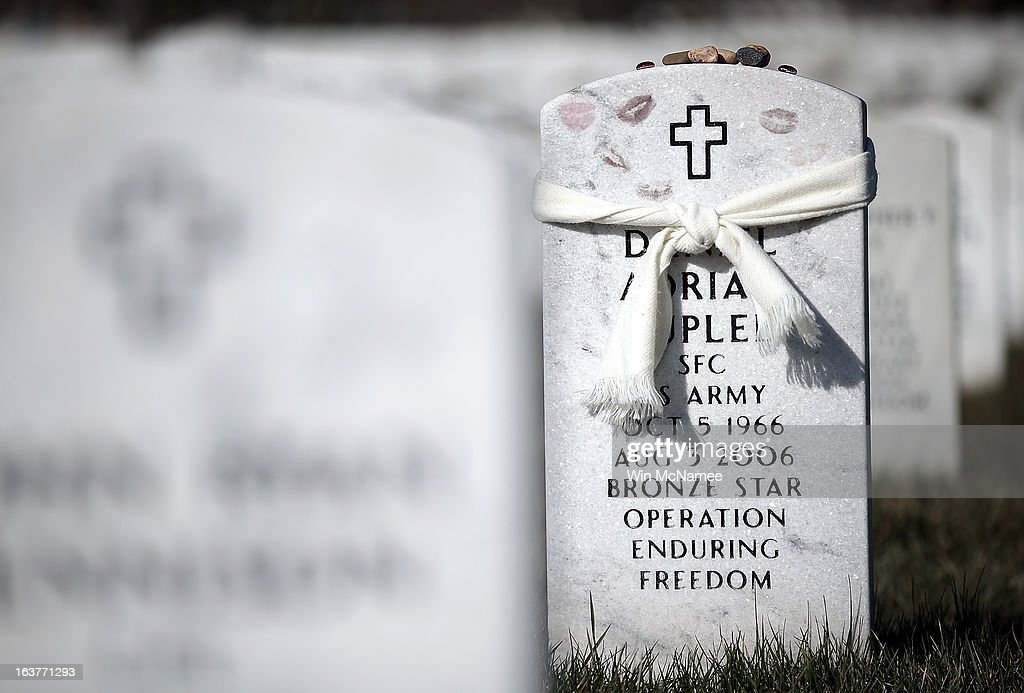 Lipstick marks and a tied scarf cover the top of the headstone of Staff Sergeant Daniel A. Suplee, of Ocala , Florida, in Section 60 at Arlington National Cemetery March 15, 2013 in Arlington, Virginia. Section 60 is the section of the cemetery where American military members killed in Iraq and Afghanistan are currently laid to rest, though soldiers and Marines from World War II through Afghanistan are also buried in the section. March 20th marks the ten-year anniversary of the beginning of the war in Iraq. Supplee died on August 3, 2006, at James A. Haley Veterans Hospital, Tampa, Florida, of injuries sustained on April 1, 2006, in Kabul, Afghanistan.