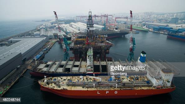Liquefied petroleum gas tankers front and a drill rig stand under construction in this aerial photograph taken above the Hyundai Heavy Industries Co...