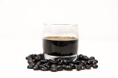 Photographic composition formed by a glass of liqueur coffee and coffee beans isolated on white.Photographic composition formed by a glass of liqueur coffee and coffee beans isolated on white.