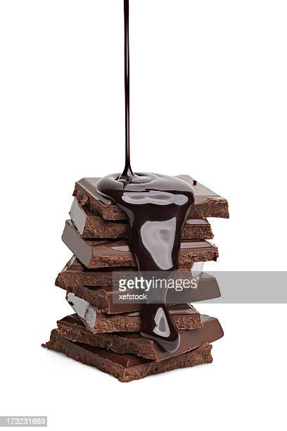 Liquid chocolate being poured on a stack of solid chocolate