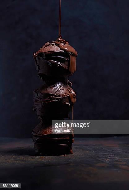 Liquid chocolate dripping on stack of three chocolate muffins