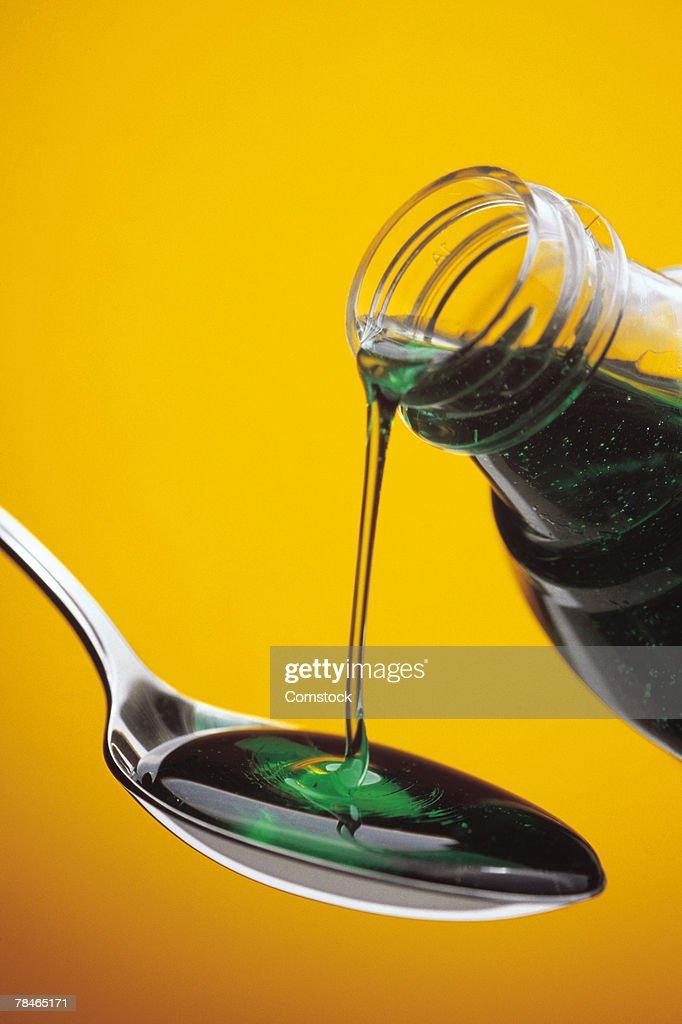 Liquid medicine being poured into spoon : Stock Photo