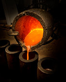Melted silver being poured into cylinders with crucible.