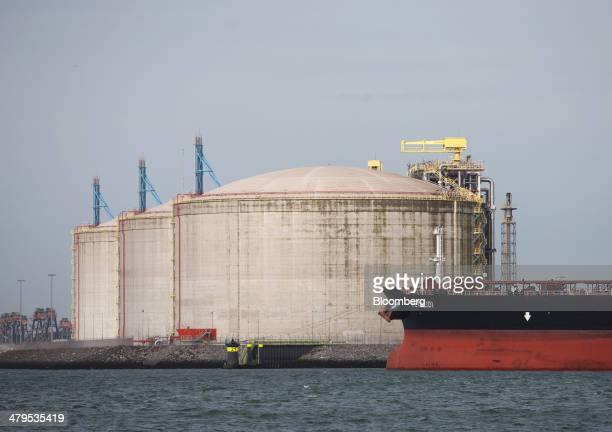 Liquid natural gas storage tanks stand on the shoreline at the Gate LNG terminal operated by Royal Vopak NV as crude oil tanker Petalidi sits moored...