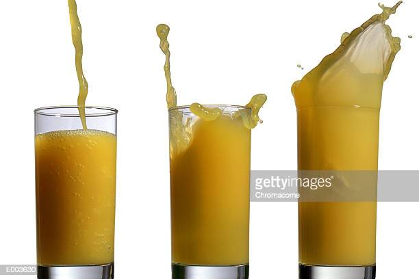 Liquid splashing out of three glasses of orange juice