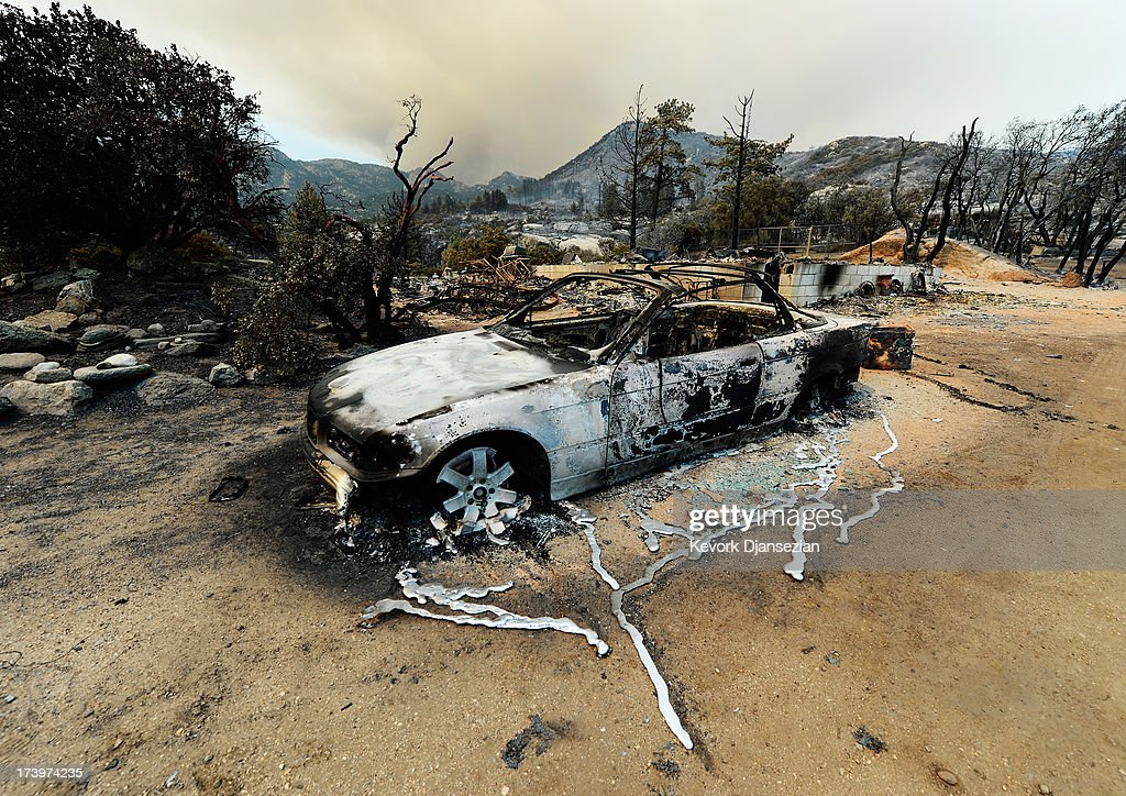 Liquified metal from a burned-out BMW car next to destroyed home is shown after the Mountian Fire scorched the area on July 18, 2013 near Idyllwild, California. The massive wildfire in Riverside county has grown to 23,000 acres and is advancing towards the mountain town of Idyllwild on one front and city of Palm Springs on the other front destroying several homs and forcing the evacuation of 6,000 people.