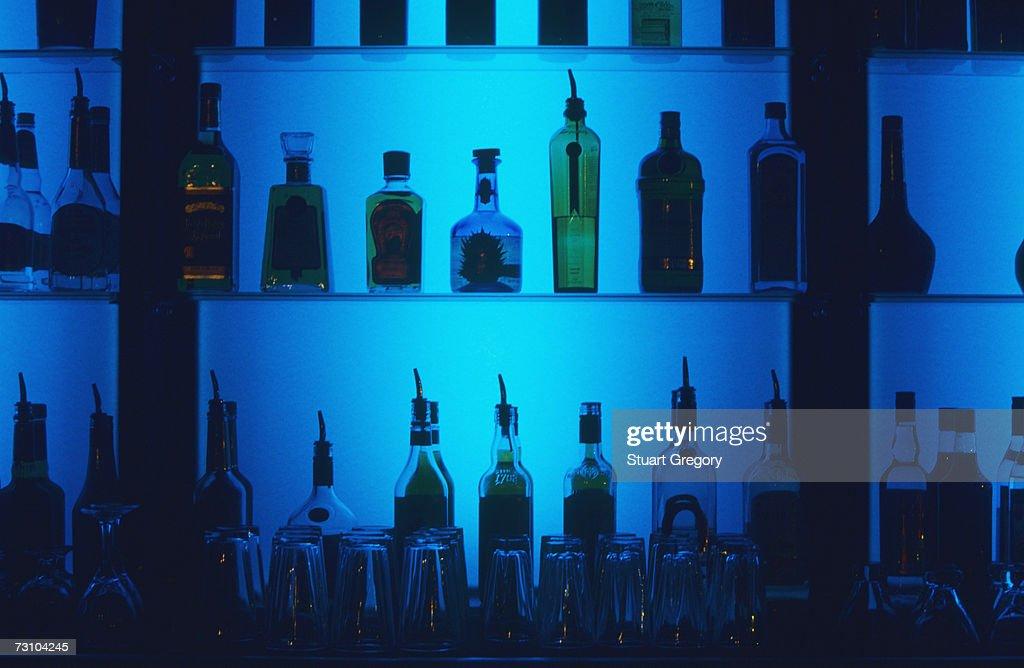 Liquor bottles on bar shelves : Stock Photo