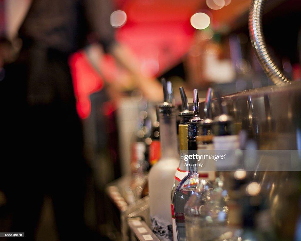 Liquor bottles rest in a bar well