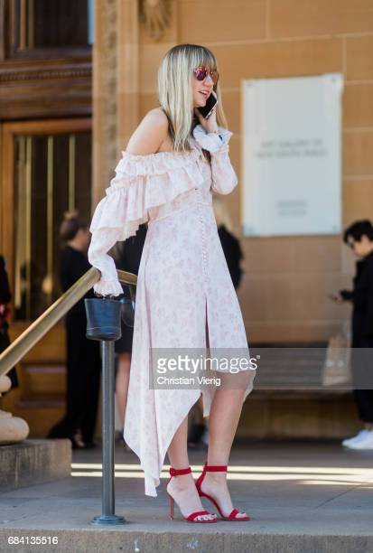 Lisa Aiken wearing an off shoulder dress heeled sandals while on the phone outside Ginger Smart at day 4 during MercedesBenz Fashion Week Resort 18...