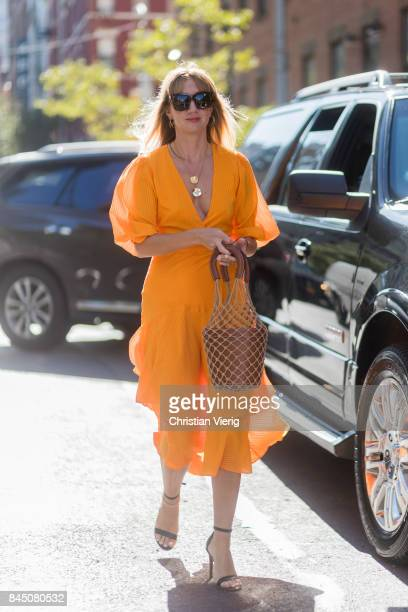 Lisa Aiken wearing an orange dress bucket bag seen in the streets of Manhattan outside SelfPortrait during New York Fashion Week on September 9 2017...