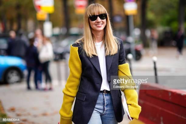 Lisa Aiken wears a blazer jacket with yellow wool sleeves denim jeans a red bag outside Lanvin during Paris Fashion Week Womenswear Spring/Summer...