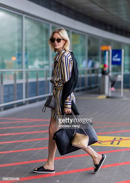 Lisa Hahnbueck at the airport wearing a striped blouse and shorts from Finders Keepers black Celine sunglasses a black scarf a black weekender bag...