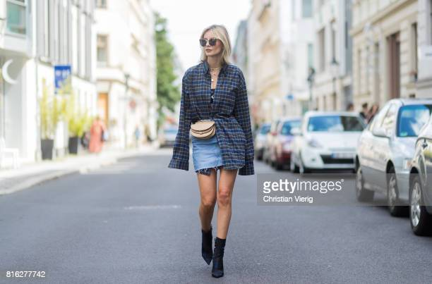 Lisa Hahnbueck wearing a checked Balenciaga men button shirt a beige Chloe belt bag a denim mini skirt Dior ankle boots sunglasses a black Calvin...