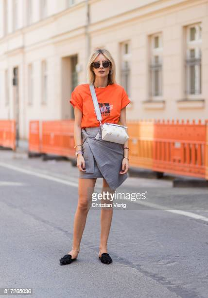 Lisa Hahnbueck wearing an orange tshirt from Urban Outfitters with the print follow the Zeitgeist a grey plaid asymmetric skirt Storets a white...