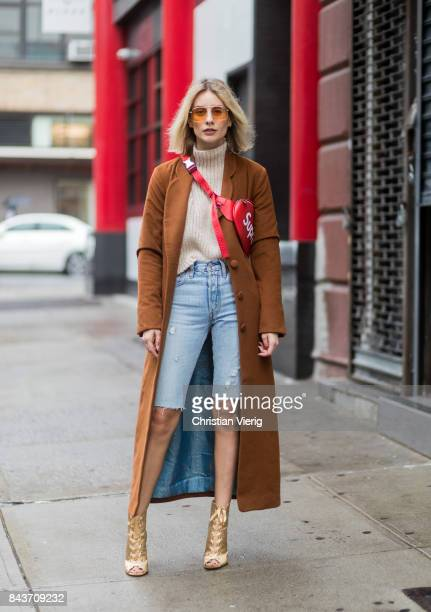 Lisa Hahnbueck wearing cropped denim shorts red Supreme x Louis Vuitton bag brown wool coat golden heels turtleneck on September 6 2017 in New York...