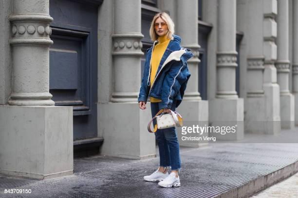 Lisa Hahnbueck wearing denim jacket yellow knit Fendi bag denim jeans white sneakers on September 6 2017 in New York City