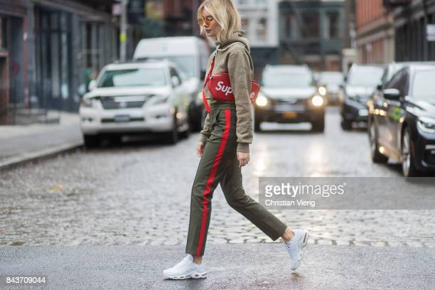 Lisa Hahnbueck wearing red Supreme x Louis Vuitton bag khaki hoody sweater pants with stripes sneakers vogue eyewear x Gigi Hadid sunglasses on...