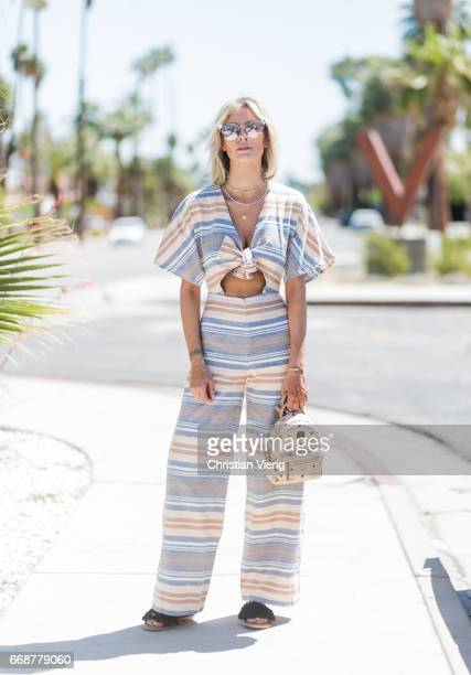 Lisa Hahnbueck wearing solid and striped jumpsuit Maxco fringe sandals MCM xmini backpack Fendi sunglasses during day 1 of the 2017 Coachella Valley...