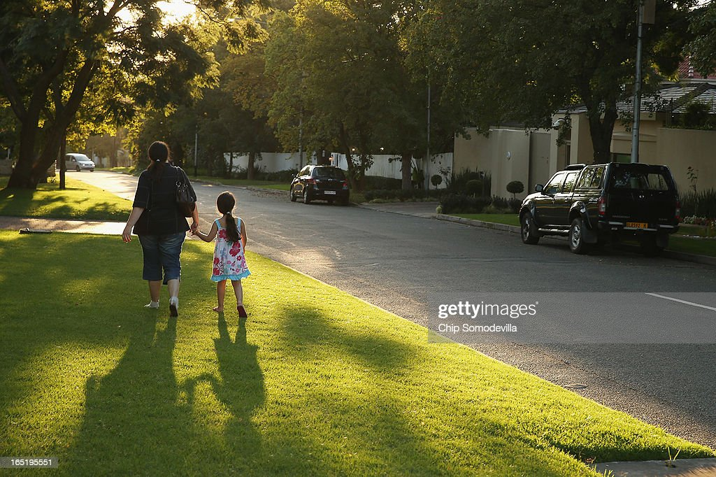 Lisa Kolman (L) and her daughter Lindy Kolman, 5, walk past former South Africa President Nelson Mandela's home after leaving goodwill messages written on stones outside the property's walls April 1, 2013 in Johannesburg, South Africa. Mandela, 94, is recovering from pneumonia in hospital, his third stay in the last four months. Referring to Mandela by clan name, Madiba, President Jacob Zuma said, 'We appeal to the people of South Africa and the world to pray for our beloved Madiba and his family and to keep them in their thoughts.' Mandela's lungs were damaged when he contracted tuberculosis during his 27 years in the infamous Robben Island prison. Mandela became the nation's first democratically elected president in 1994 following the end of apartheid.