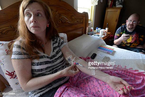 Lisa Lawlor of Saco who is suffering from Lyme disease adjusts her IV as she takes antibiotics in her bed Monday August 18 2014 Looking on is her...