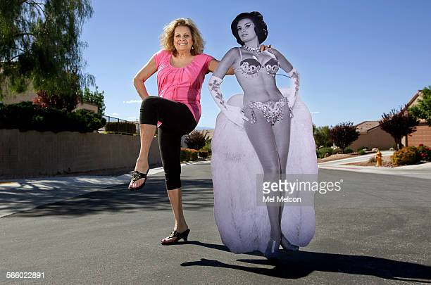 Lisa Malouf Medford poses next to a life size publicity photograph of her taken back in 1959 when she was a nude show girl for the Folies Bergere at...