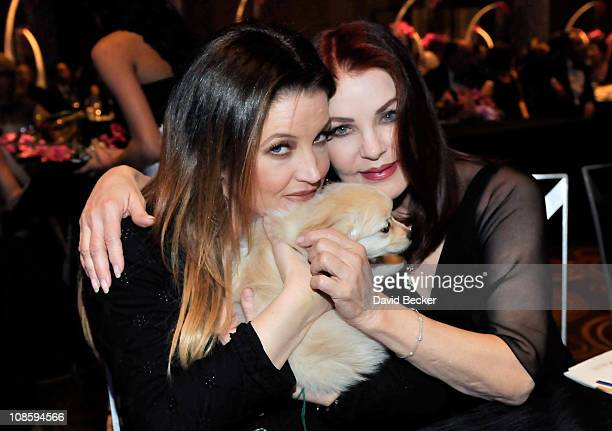 Lisa Marie Presley and her mother Priscilla Presley cuddle a threemonthold cockapoo puppy during annual Black White Ball fundraising event for the...