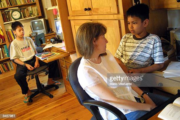 Lisa McLean speaks with her adopted son James while her other adopted son Johnny studies his lesson at their home April 22 2004 in Shreveport...