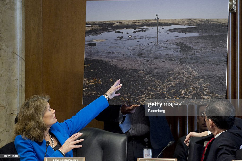 Lisa Murkowski, a Republican from Alaska, left, points to a photograph of an abandoned Alaskan oil well during a Senate Energy and Natural Resources Committee confirmation hearing for Sally Jewell, president and chief executive officer of Recreational Equipment Inc. (REI) and nominee for U.S. Interior secretary, not pictured, in Washington, D.C., U.S., on Thursday, March 7, 2013. Jewell disclosed she owns shares in companies such as ConocoPhillips and Exxon Mobil Corp., which hold drilling leases managed by the Interior Department. Photographer: Andrew Harrer/Bloomberg via Getty Images