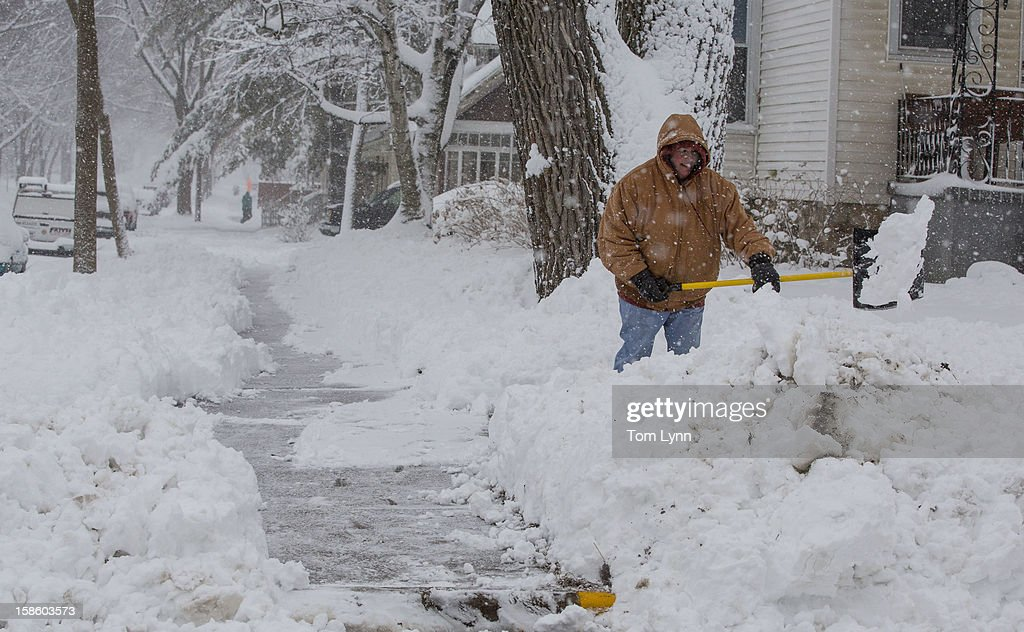 Lisa Schultz shovels her sidewalk during a winter storm December 20, 2012 in Baraboo, Wisconsin. The State Patrol had warned motorists to stay home as a paralyzing winter storm bore down on Wisconsin, the first significant snowstorm to hit southern Wisconsin in two winters.