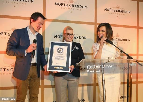Lisa Wilkinson and Tyson Stelzer pose alongside a Guiness representative holding a certificate for 'Lasting Champagne Tasting Event' at Sydney Opera...
