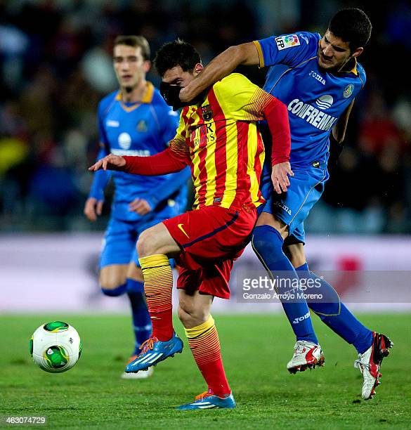 Lisandro Ezequiel Lopez of Getafe CF holds the face of Lionel Messi of FC Barcelona during the Copa del Rey Round of 8 second leg match between...