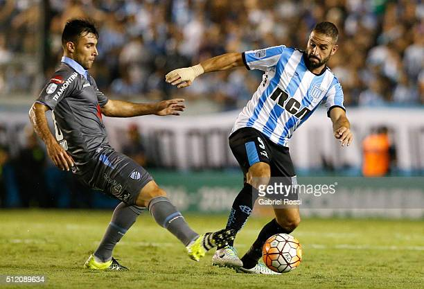 Lisandro Lopez of Racing Club fights for the ball with Danny Bejarano of Bolivar during a group stage match between Racing Club and Bolivar as part...