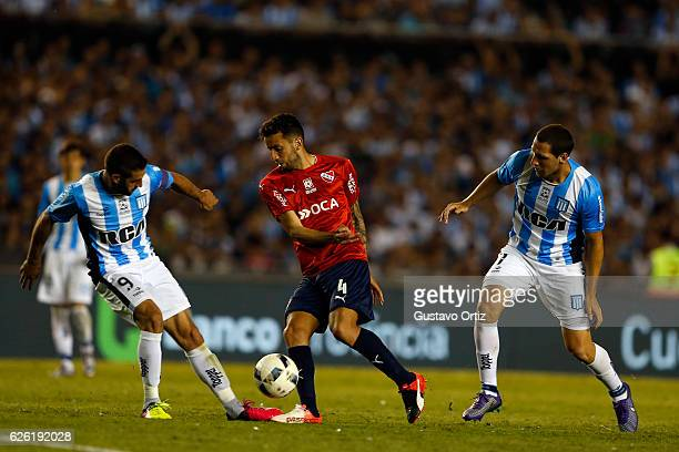 Lisandro Lopez of Racing Club fights for the ball with Jorge Ortiz of Independiente during a match between Racing Club and Independiente as part of...