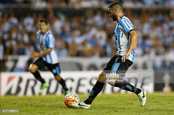 Lisandro Lopez of Racing Club passes the ball to Marcos Acuña of Racing Club to scores the fourth goal of his team during a group stage match between...