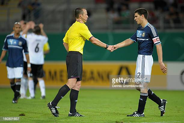 Lisandro Magallan of Argentina and referee Ruddy Buquet shake hands after the Under 21 international friendly match between Germany U21 and Argentina...