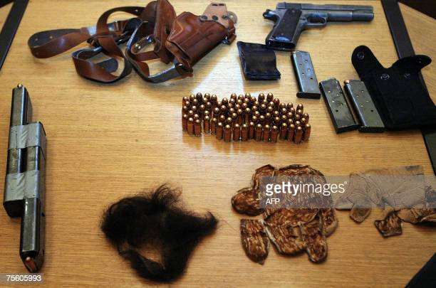 An automatic pistol a holster ammunitions several clips a false beard and moustache are displayed on the table during a press conference at the...