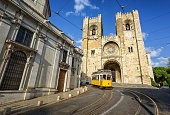Old tram in front of cathedral in Lisbon, Portugal