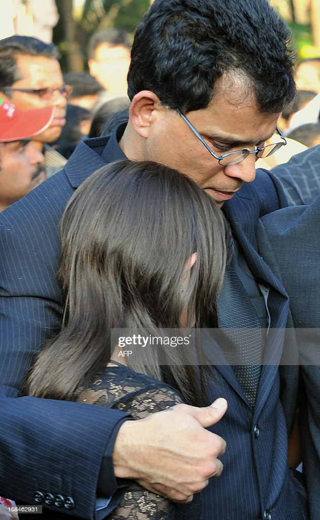 Lisha Saldanha (L), daughter of late nurse Jacintha Saldanha, is consoled by her father Benedict Barbosa during her mother's funeral at The Shirve Church cemetary near Mangalore on December 17, 2012. About 2,000 mourners have packed a Catholic church in southwest India for the funeral of the nurse who was found hanged after taking a hoax call to the hospital treating Prince William's wife. Indian-born Jacintha Saldanha, 46, apparently committed suicide after answering the telephone call from Australian radio DJs to the hospital where the pregnant Duchess of Cambridge was admitted with acute morning sickness. AFP PHOTO/Manjunath KIRAN