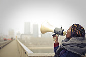 Young, african woman is using a loudspeaker