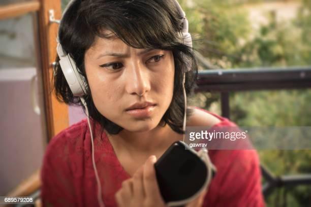 Listening podcast through headphones.